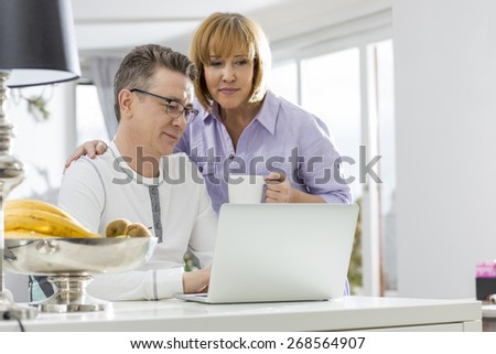 Mature couple using laptop together at table in house - stock photo
