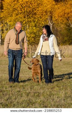 Mature couple walking retriever dog enjoying autumn sunny park - stock photo