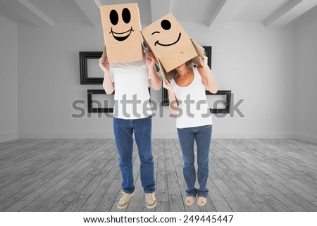 Mature couple wearing boxes over their heads against big room with several frames at wall - stock photo