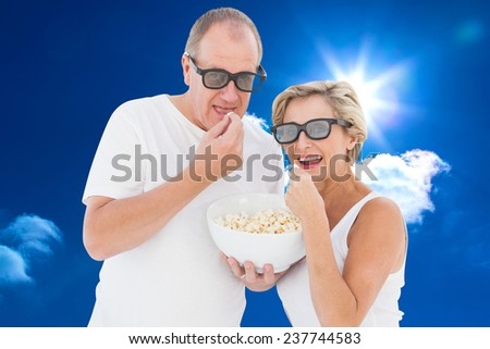 Mature couple wearing 3d glasses eating popcorn against bright blue sky with clouds - stock photo