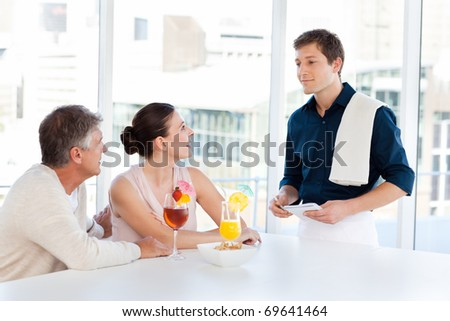 Mature Couple with a waiter in a bar - stock photo