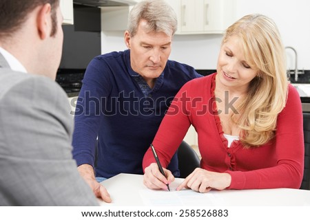 Mature Couple With Financial Adviser Signing Document At Home - stock photo