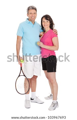 Mature couple with tennis rackets. Isolated on white - stock photo