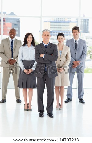 Mature director smiling and crossing his arms in front of his team - stock photo