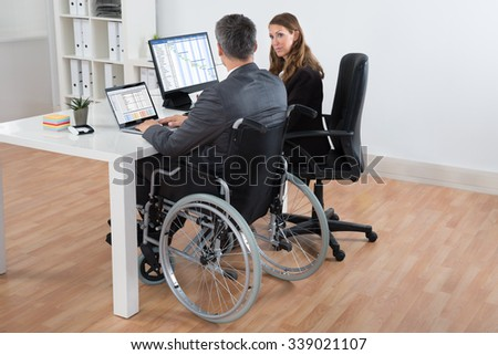 Mature Disabled Businessman And Businesswoman Working Together On Computer In Office - stock photo