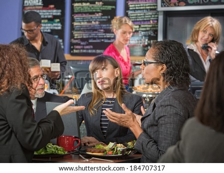 Mature diverse group of adults talking in indoor cafe - stock photo