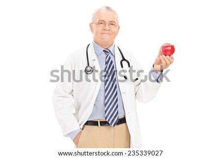 Mature doctor holding a ripe apple isolated on white background - stock photo