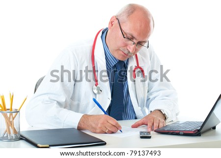 mature doctor in blue shirt and coat sits at his desk, make some notes, isolated on white background - stock photo