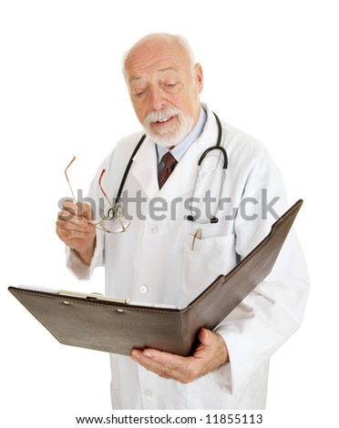 Mature doctor reading a patients chart.  Isolated on white. - stock photo
