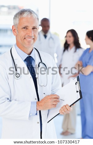 Mature doctor showing a great smile while pointing to a word on his clipboard - stock photo