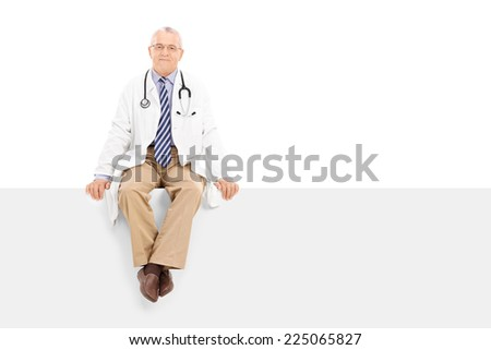 Mature doctor sitting on a blank panel isolated on white background - stock photo