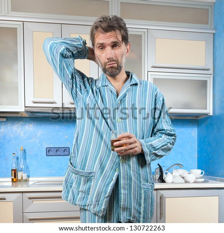 mature drunk man standing in pajamas with glass - stock photo