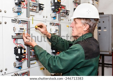 Mature electrician working in white hard hat with cables and wires. Russian people in Russia. Screwdriver in hand - stock photo