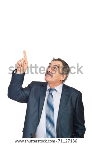 Mature executive man pointing upwards to copy space and looking up isolated on white background - stock photo