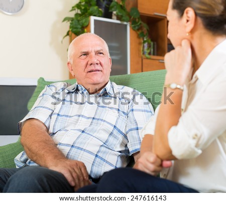 mature family having serious talking in home interior - stock photo