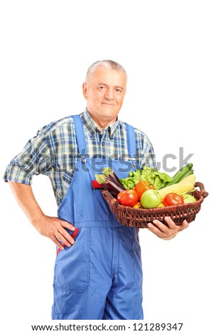 Mature farmer holding a basket full of fresh vegetables isolated against white background - stock photo