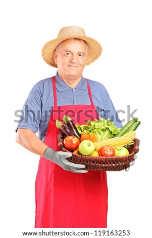 Mature farmer man holding a basket with fresh vegetables isolated on white background - stock photo