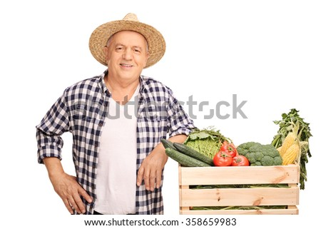 Mature farmer posing next to a wooden crate full of fresh vegetables isolated on white background - stock photo