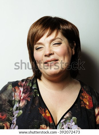 mature fat cheerful smiling woman close up isolated in studio - stock photo