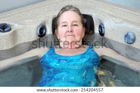 Mature female beauty relaxing in hot tub outdoors. - stock photo