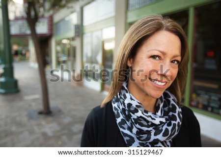 Mature female business owner standing in front of store - stock photo