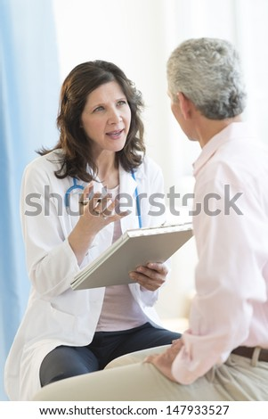 Mature female doctor discussing with patient in clinic - stock photo