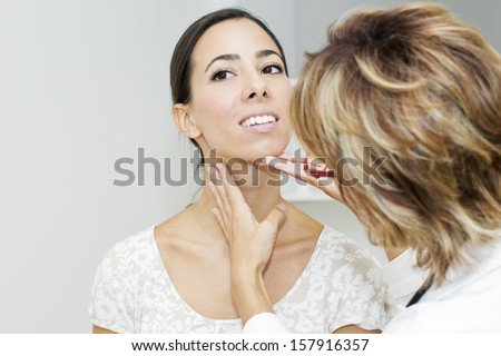 Mature female doctor examining her patient. - stock photo