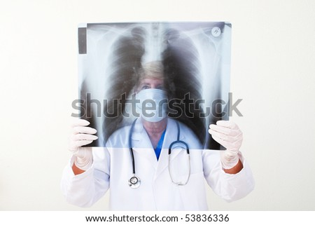 mature female doctor examining patient's x ray - stock photo