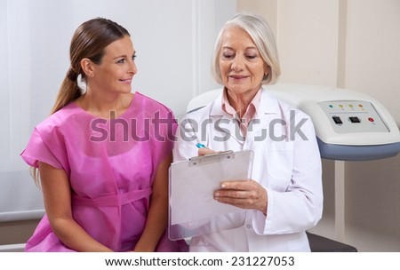 Mature female doctor explaining medical tests to happy woman patient. Health concept. - stock photo