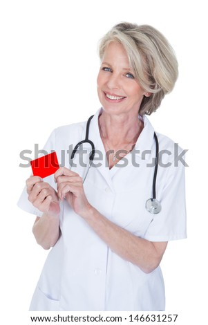Mature Female Doctor Holding Visiting Card Over White Background - stock photo