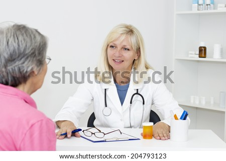Mature female doctor talking with her senior patient. - stock photo