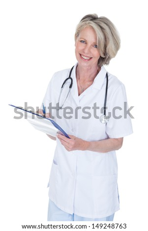 Mature Female Doctor Writing On Clipboard Over White Background - stock photo