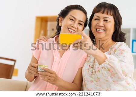 Mature female friends taking selfie with the smart phone - stock photo