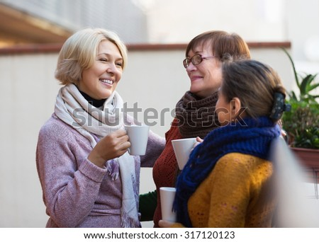 Mature female in warm clothes having cup of hot tea on terrace - stock photo