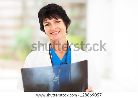 mature female medical doctor with x ray - stock photo