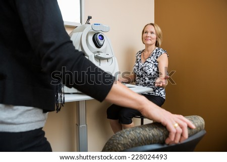 Mature female optician asking patient to sit in eye clinic - stock photo