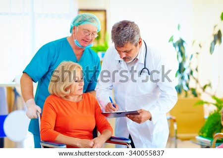 mature female patient on wheelchair listens to doctor prescription medication - stock photo