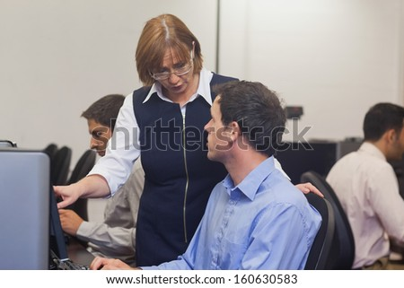 Mature female teacher talking to a student in computer class - stock photo