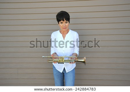 Mature female trumpet master with her horn outside. - stock photo