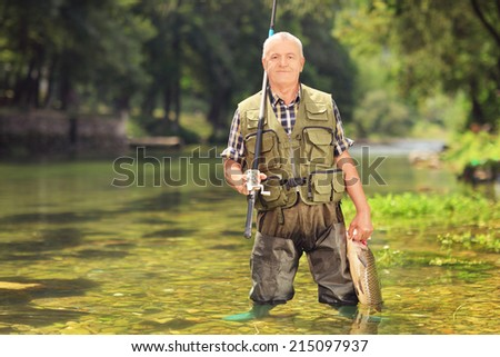 Mature fisherman holding a fish and fishing rod in a river  - stock photo