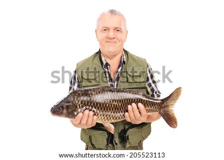 Mature fisherman holding a fresh fish isolated on white background - stock photo