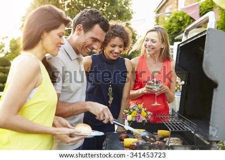Mature Friends Enjoying Outdoor Summer Barbeque In Garden - stock photo