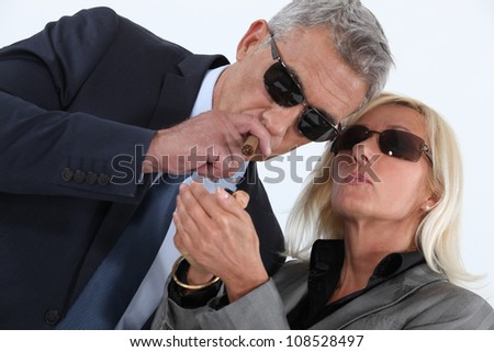mature gentleman smoking cigar with blonde spouse showing off - stock photo