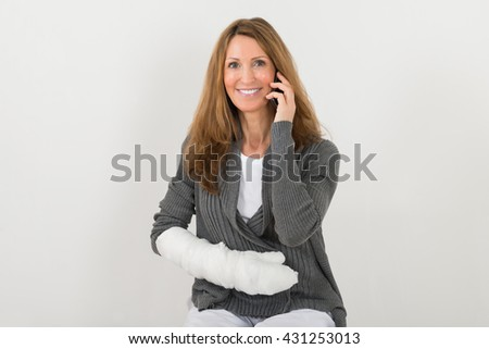 Mature Happy Woman With Broken Hand Talking On Mobile Phone - stock photo