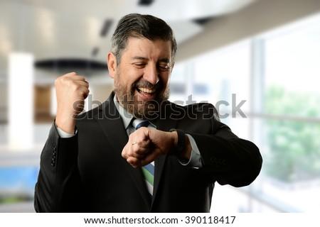 Mature hispanic businessman celebrating inside an office building - stock photo