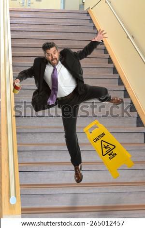 Mature Hispanic businessman falling on stairs - stock photo