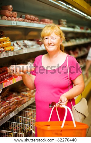 Mature Housewife buying sausage in supermarket - stock photo
