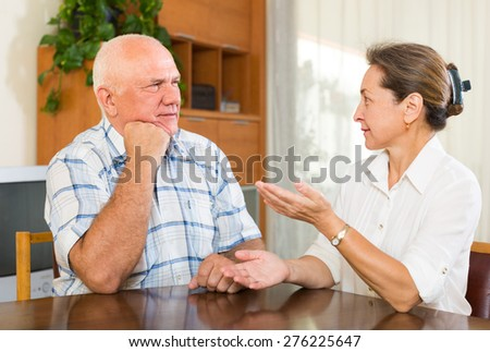 mature  husband and wife  having serious talking in home interior - stock photo