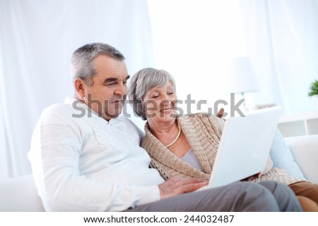 Mature husband and wife using laptop - stock photo