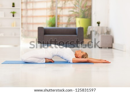 mature lady doing yoga at home - stock photo
